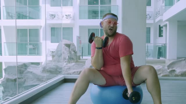 Funny fat male in pink glasses and in a pink t-shirt is engaged with dumbbells on a fit ball in the gym depicting a girl