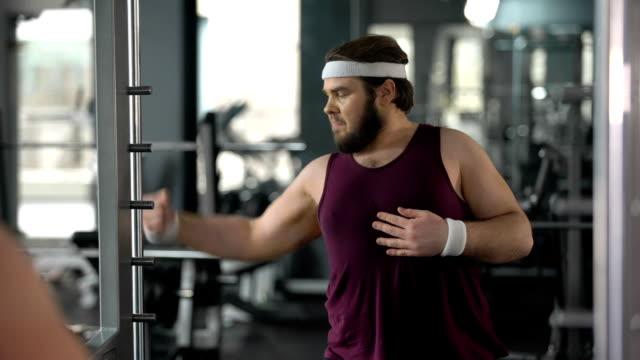 vídeos de stock, filmes e b-roll de homem gordo engraçado olhar para ginásio de reflexão do espelho e posando, fingindo muscular - humor