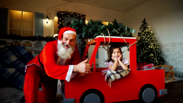 Funny Father Christmas doing thumbs up near gladden little princess with waving hand video
