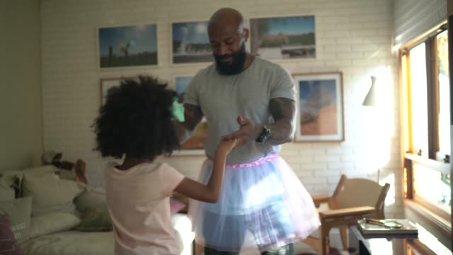 vídeos de stock e filmes b-roll de funny father with tutu skirts dancing like ballerinas - home