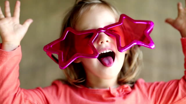 Funny girl in big glasses in the shape of stars looks at the camera and grimaces video