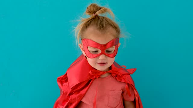 vídeos de stock e filmes b-roll de funny girl in red superhero costume with mask waves hand - baby super hero