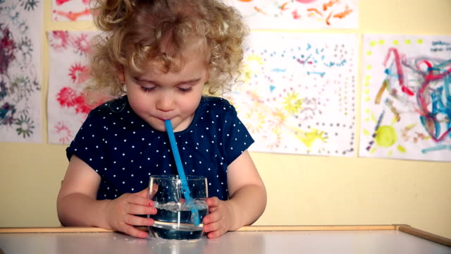 Funny girl play with straw and glass of water sitting by table in her room video