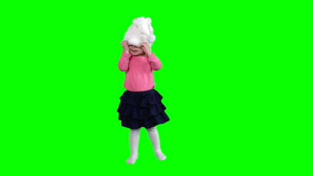 funny girl with curly hair put white santa hat isolated on green video