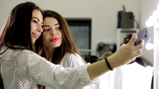 ビューティー サロンでスマート フォンを使用して selfie を作って面白い女の子 - 美容室のビデオ点の映像素材/bロール