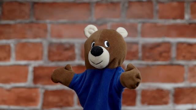 Funny glove bear over brick wall