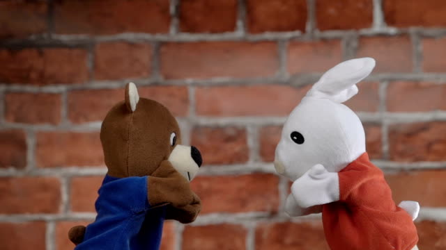 Funny glove puppets over brick background