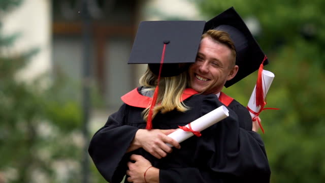 Funny graduate hugging his female friend and laughing, achievement, happy future video