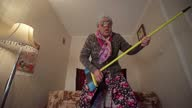 istock Funny grandmother plays the mop like a guitar.  Funny face with big glasses. 1283258683