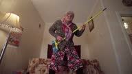 istock Funny grandmother plays the mop like a guitar. 1283258672