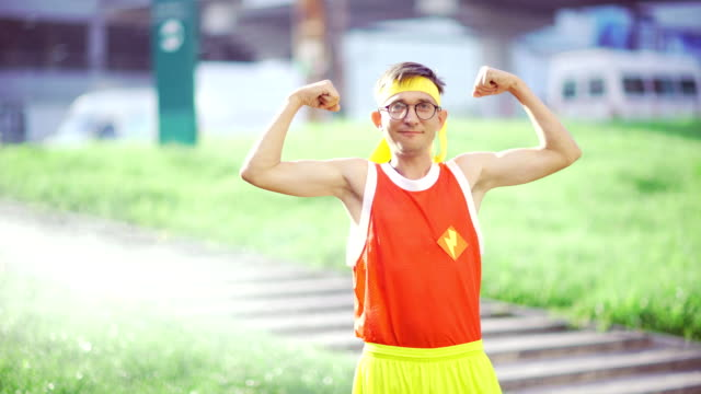 funny guy freak smiling showing muscles in hands after workout i - chudy filmów i materiałów b-roll