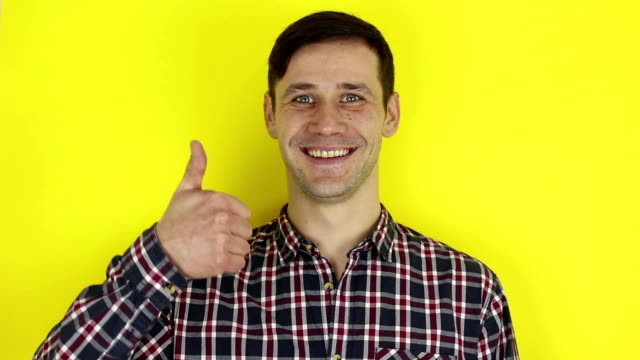 Funny handsome guy smiles and shows thumb up. Portrait on yellow background.