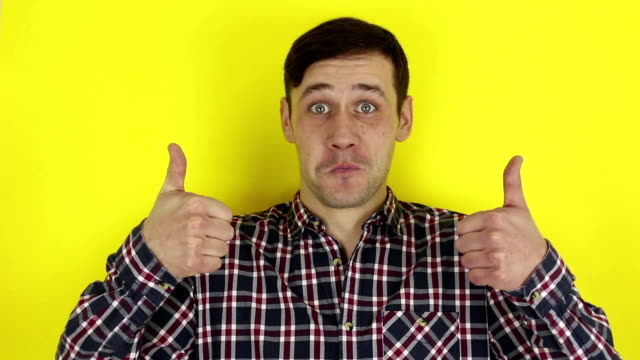 Funny handsome guy smiles and shows thumb up with both hands. Portrait on yellow background.