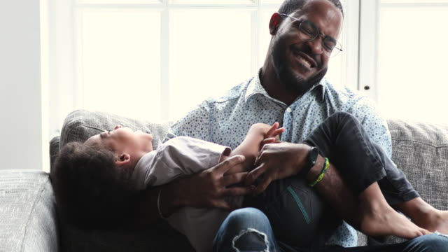 divertente felice papà africano solletico simpatico piccolo figlio sul divano - fare il solletico video stock e b–roll