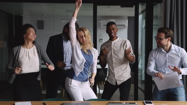 lustiges fröhliches business-team tanzt zusammen auf firmenparty - motivation stock-videos und b-roll-filmmaterial