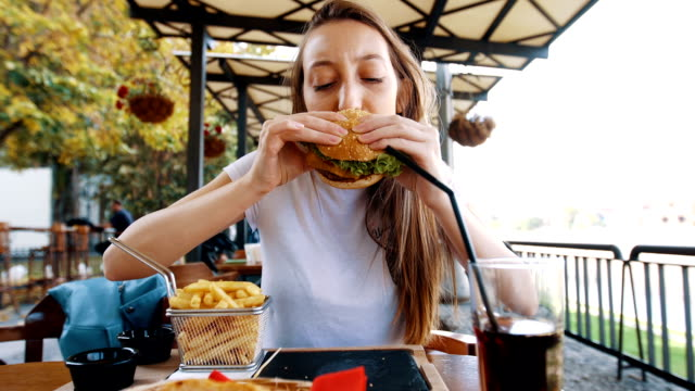 Funny hungry woman biting her burger There is one young woman age 22. She is in the outdoor restoraunt and she eat a burger, fries and drink soda. She enjoy it. eating stock videos & royalty-free footage