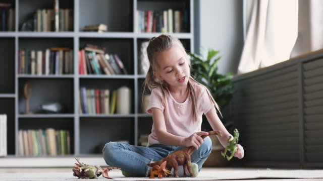 vidéos et rushes de fille drôle d'enfant ayant l'amusement jouant des dinosaures s'asseyant sur le tapis - une seule petite fille
