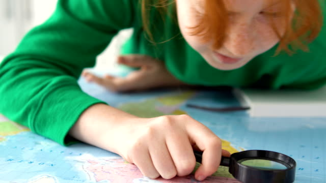 vídeos de stock e filmes b-roll de funny kid searching own country on world map. child looking for travel place - cartografia