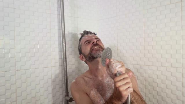 vídeos y material grabado en eventos de stock de divertido estilo de vida de joven atractivo y hombre feliz con barba cantando en la ducha despreocupada bailando loco en casa fingiendo un micrófono disfrutando de excitado - ducha