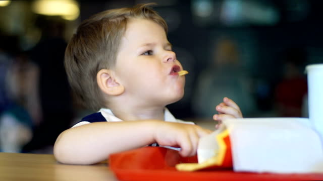 Funny little boy eating french fries in restaurant. video