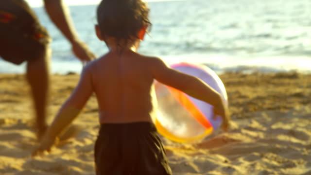 Funny little boy jumps on a beach ball