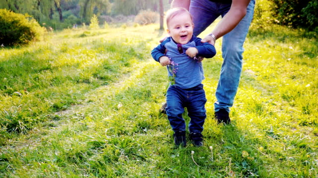 Funny little boy learns to walk. His hands are supported by his father. The boy laughs, holds a lilac flower in his hands. Slow motion video video