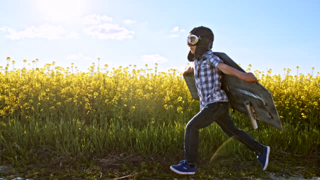 SLO MO Funny little boy running on a dirt road in a jet pack costume Slow motion side view tracking shot of a little boy wearing jet pack costume while running down a dirt road in the countryside. Slovenia boys stock videos & royalty-free footage