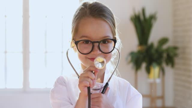Funny little child girl wear medical uniform playing doctor, portrait