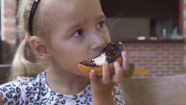 funny little girl eating sweet chocolate donut at table in cafe. face cute blond girl biting chocolate doughnut at dessert in restaurant - bombolone video stock e b–roll