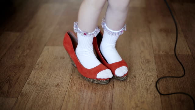 Funny little girl in a in mother's shoes Funny little girl in a in mother's shoes shoe stock videos & royalty-free footage