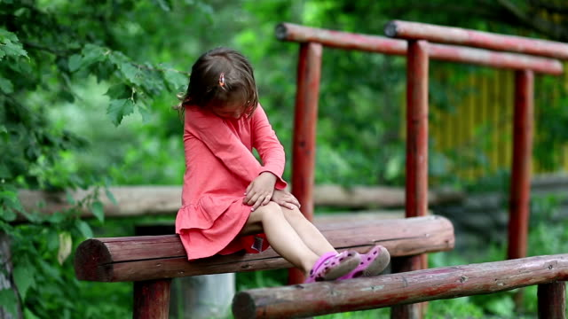 Funny little girl sits on a wooden log at a sports ground video