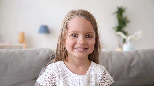 rolig liten flicka leende tittar på kamera att göra video samtal - förskoleelev bildbanksvideor och videomaterial från bakom kulisserna