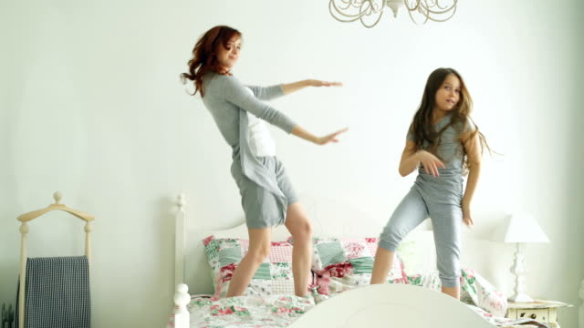 vídeos de stock e filmes b-roll de funny little girl with her loving mother have fun dancing modern style together jumping on bed during morning at home - crianças todas diferentes