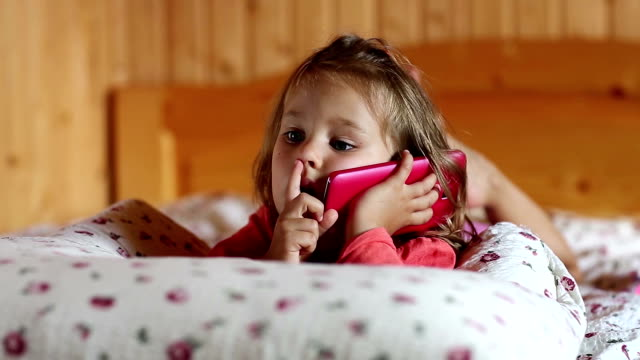 Funny little girl with red smartphone lies on the bed and picks his nose Funny little girl with red smartphone lies on the bed and picks his nose. Little girl lies on the pillow and holds in hands mobile phone. Little girl with red cell phone lies on the sofa telephone receiver stock videos & royalty-free footage