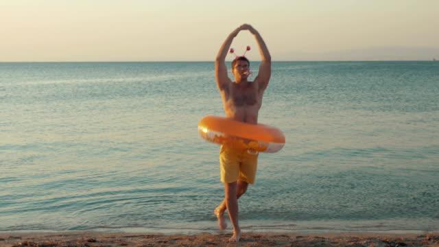 vídeos de stock, filmes e b-roll de dança engraçada do homem na praia - inflável
