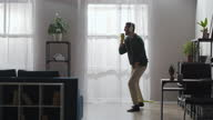 istock funny man is singing into mop during clean-up at home, listening to music by headphones, dancing 1300960439