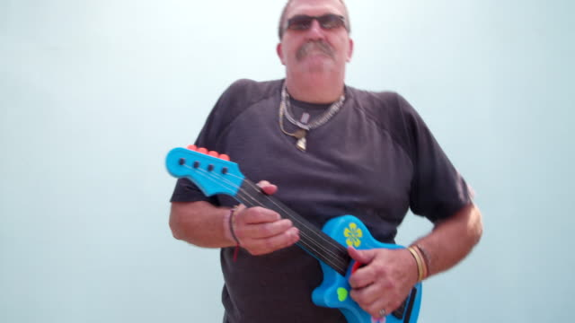 Funny man playing children's toy guitar Silly senior man playing children's toy guitar and making funny faces, isolated on blue wall background rocking chair stock videos & royalty-free footage