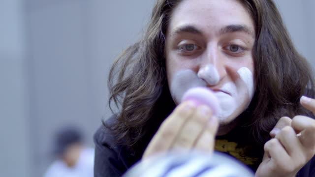 funny mime applying white paint on his face - гримировальные краски стоковые видео и кадры b-roll