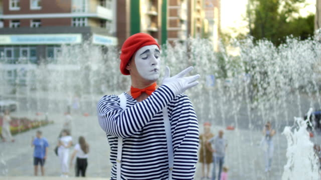 Funny mime conducting and has fun at the fountain background Funny mime in red beret has a performance at fountain background and moving his hands as a conductor. Man wearing stripped shirt is an street actor and playing funny scenes for people. greasepaint stock videos & royalty-free footage