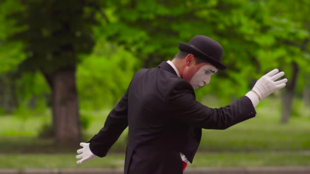Funny mime does perfomance in the park Mime in black hat, suit, white shirt and red bow do performance in park. Funny man walks moon walk and straightens clothes. Performance of street artist. Portrait of comic playing with facial expressions and gestures greasepaint stock videos & royalty-free footage