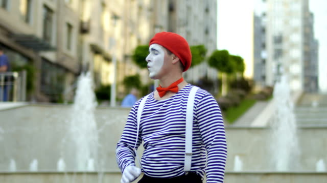 Funny mime in red beret gesticulate hands at fountains background Funny mime in red beret has a performance at fountain background and moving his hands as a conductor. Man wearing stripped shirt is an street actor and playing funny scenes for people. greasepaint stock videos & royalty-free footage