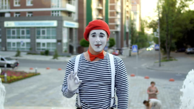 Funny mime in red beret show thumb up at fountain background Funy mime in red beret and stripped shirt is posing for camera at fountains background. Street artist gesticulating hands and his expressions on camera. The mime is standing at the background of the city square with fountains. greasepaint stock videos & royalty-free footage