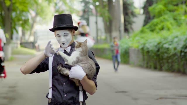 funny mime joking with cat on the street - гримировальные краски стоковые видео и кадры b-roll