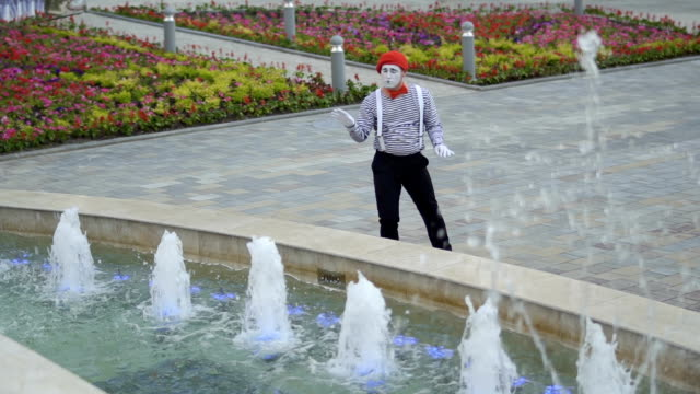 Funny mime move his hands as a conductor and control the fountains Funny mime in red beret has a performance at fountain background and moving his hands as a conductor. Man wearing stripped shirt is an street actor and playing funny scenes for people. greasepaint stock videos & royalty-free footage