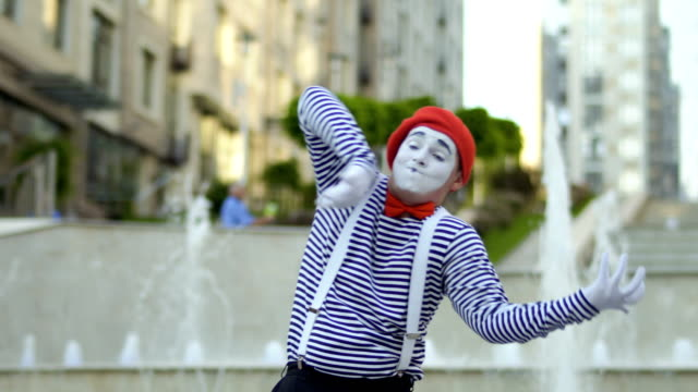 Funny mime playing at violin at fountains background Funny mime in red beret preparing to performance at fountains background and start playing on invisible violin. Man wearing stripped shirt is an street actor and playing funny scenes for people. greasepaint stock videos & royalty-free footage