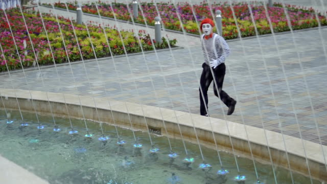 Funny mime want to dive into fountain Funy mime in red beret and stripped shirt is posing for camera at fountains background. Street artist want to dive into fountain. The mime is standing at the background of the city square with fountains. greasepaint stock videos & royalty-free footage