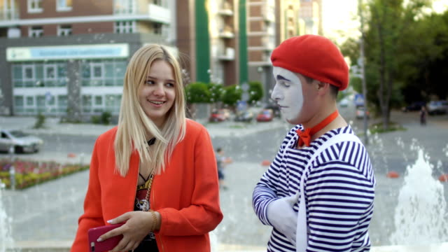 Funny mime with beautiful young girl at fountains background Mime in red beret and stripped shirt has fun with young girl at fountain background. Street actor entertains passers-by. greasepaint stock videos & royalty-free footage