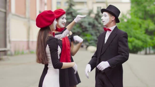 Funny mimes is crooking in the city Company of three mimes, man and women in black dress do perfomance in the city. Girls actors is trying hard to catch each other hands, whan they do it ladies make sigh of relief and relax. Man mime shows his dissatisfy. Performance of street artists. greasepaint stock videos & royalty-free footage