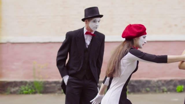 funny mimes make perfomance near building - гримировальные краски стоковые видео и кадры b-roll