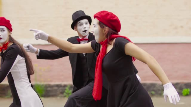 Funny mimes make perfomance near building Company of three mimes, man and women in black dress do perfomance near building. Actors pull each other slowly in different sides and grimaced. Performance of street artists. Portrait of comics playing with facial expressions and gestures. greasepaint stock videos & royalty-free footage